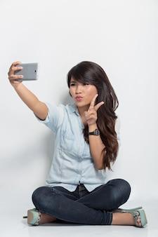 Jovem mulher sentada no chão a tirar auto-câmara