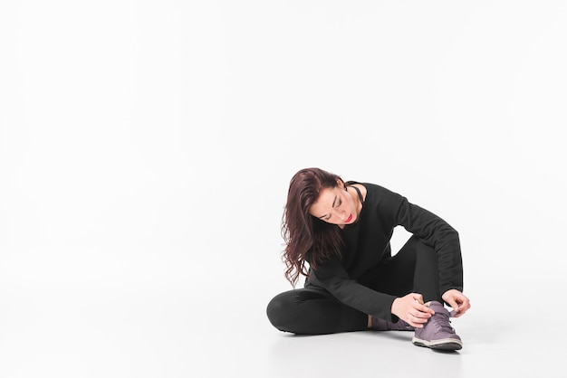 Jovem mulher sentada no chão, colocando a alça de sapato contra fundo branco