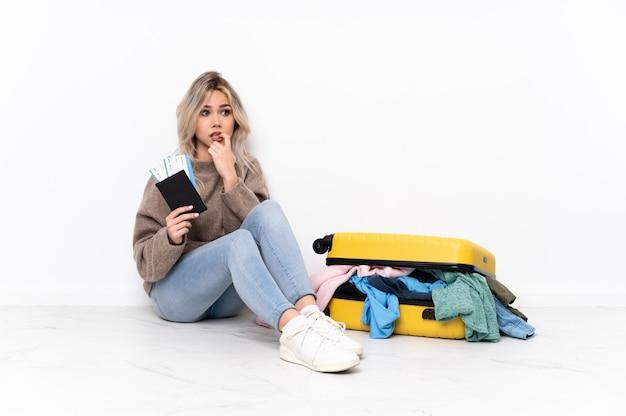 Jovem mulher sentada no chão com mala