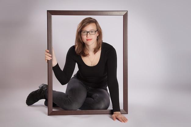 Jovem mulher sentada no chão com uma moldura