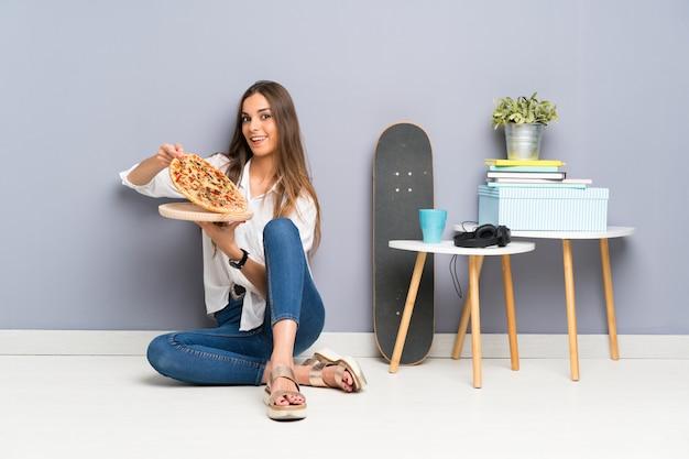 Jovem mulher sentada no chão com uma pizza