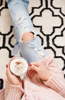Jovem mulher sentada no chão com uma xícara de café