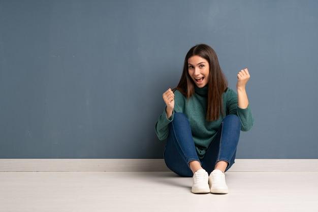 Jovem mulher sentada no chão comemorando uma vitória na posição de vencedor
