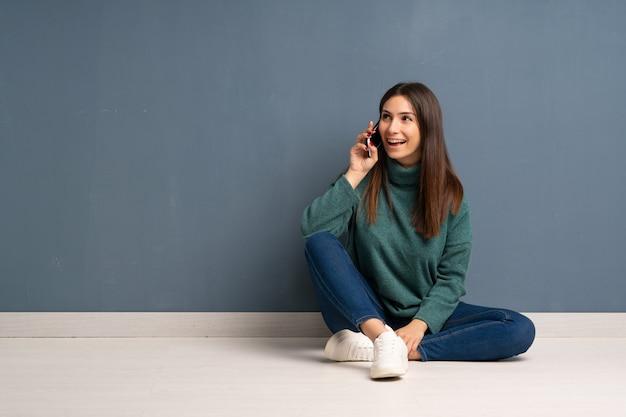 Jovem mulher sentada no chão conversando com o telefone celular