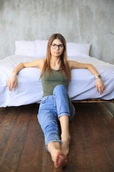 Jovem mulher sentada no chão do quarto