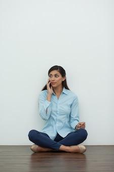 Jovem mulher sentada no chão e que convida o telefone