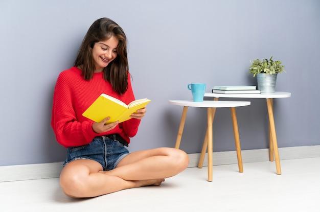 Jovem mulher sentada no chão e segurando um caderno