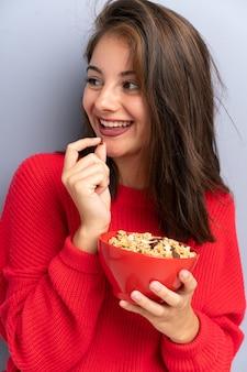 Jovem mulher sentada no chão e segurando uma tigela de cereais