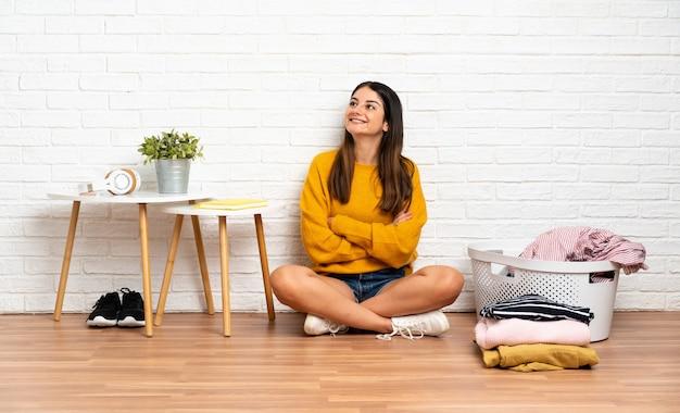 Jovem mulher sentada no chão em ambientes fechados com cesto de roupas, olhando para cima enquanto sorrindo