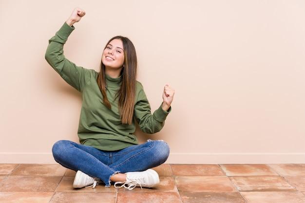 Jovem mulher sentada no chão, mostrando o gesto de força com os braços, símbolo do poder feminino