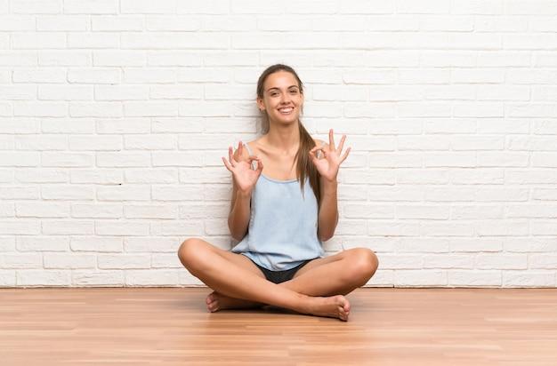 Jovem mulher sentada no chão mostrando um sinal de ok com os dedos