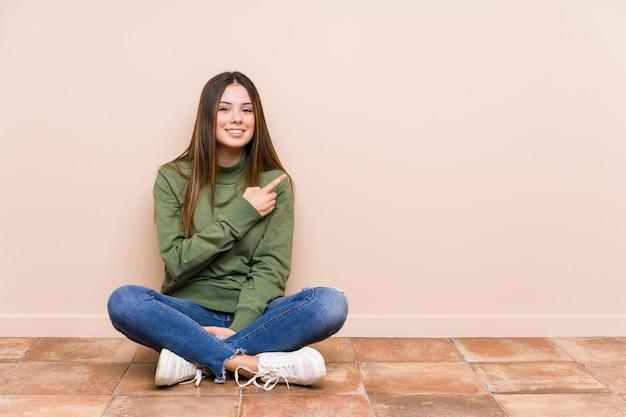 Jovem mulher sentada no chão, sorrindo e apontando para o lado, mostrando algo no espaço em branco