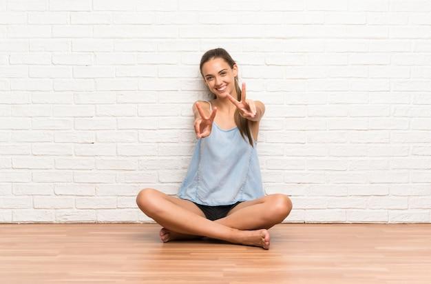 Jovem mulher sentada no chão sorrindo e mostrando sinal de vitória