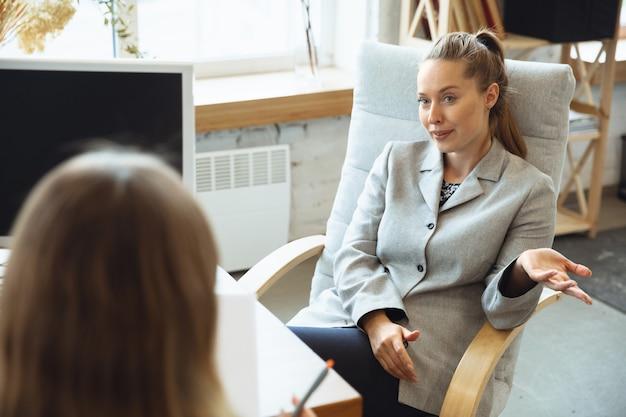 Jovem mulher sentada no escritório durante a entrevista de emprego com uma funcionária, chefe ou gerente de rh, falando, pensando, parece confiante. conceito de trabalho, obtenção de emprego, negócios, finanças, comunicação.