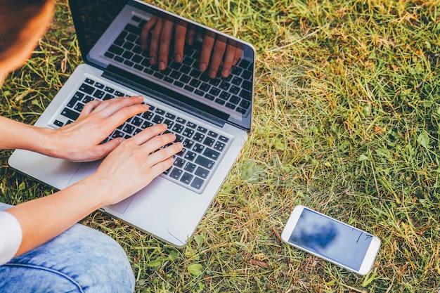 Jovem mulher sentada no gramado verde parque da cidade, trabalhando no computador pc laptop