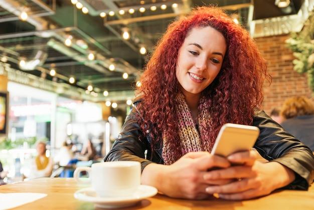 Jovem mulher sentada no interior no moderno café urbano, escrevendo com seu telefone celular.