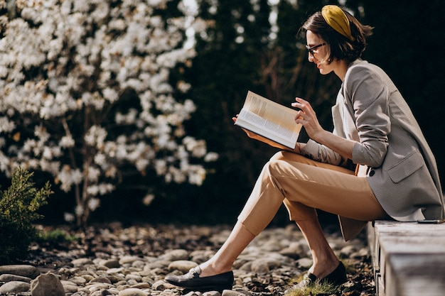 Jovem mulher sentada no quintal e lendo o livro