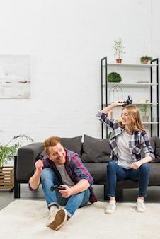Jovem mulher sentada no sofá batendo o namorado com joystick