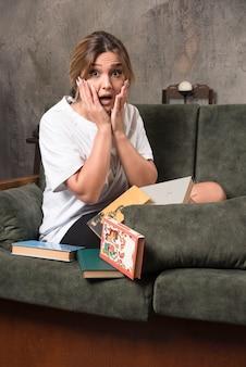 Jovem mulher sentada no sofá cheio de livros parece surpresa.