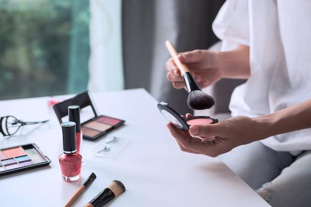 Jovem mulher sentada no sofá e fazendo maquiagem em casa