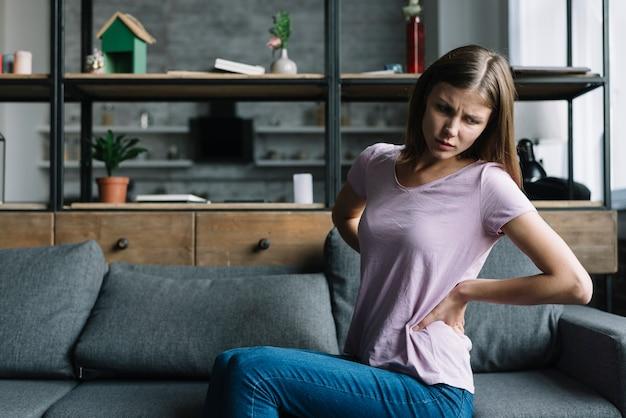 Jovem mulher sentada no sofá sofrendo de dor nas costas
