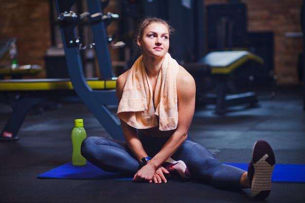 Jovem mulher sentada no tapete com uma toalha em volta do pescoço e descansando no ginásio