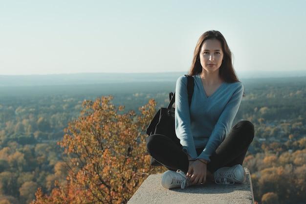 Jovem mulher sentada no topo de uma colina no fundo da natureza. ponto de vista. retrato.
