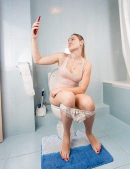Jovem mulher sentada no vaso sanitário e fazendo selfie