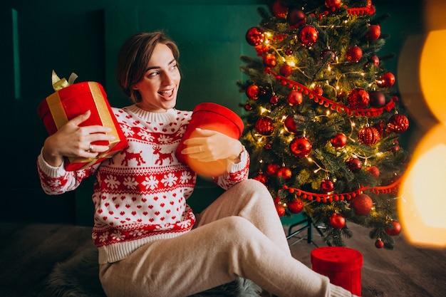 Jovem mulher sentada perto da árvore de natal com caixas vermelhas