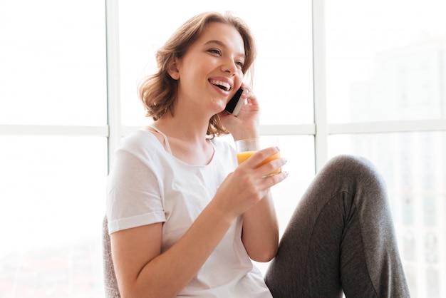 Jovem mulher sentada perto da janela, bebendo suco falando por telefone