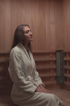 Jovem mulher sentada relaxada em uma sauna de madeira