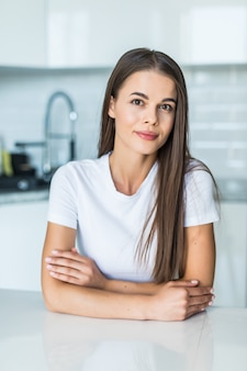 Jovem mulher sentada uma mesa na cozinha.