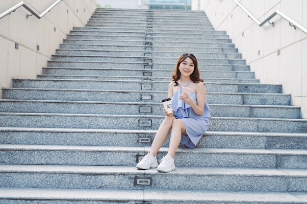 Jovem mulher sente-se e usando o telefone inteligente na escada ao ar livre, estilo de vida da mulher moderna.