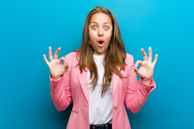 Jovem, mulher, sentindo-se chocado, surpreso e surpreso, mostrando aprovação fazendo sinal de bem com as duas mãos