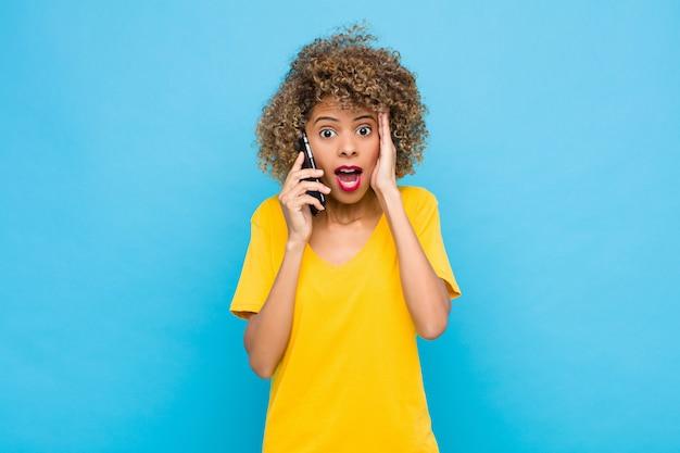 Jovem, mulher, sentindo-se feliz, animado e surpreso, olhando para o lado com as duas mãos no rosto com um telefone móvel