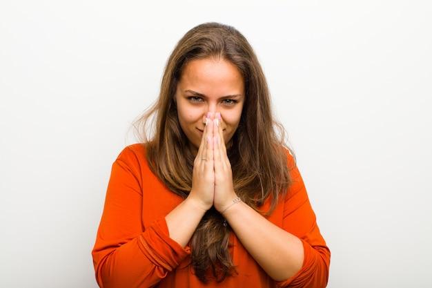 Jovem, mulher, sentindo-se preocupada, esperançosa e religiosa, orando fielmente com as palmas das mãos pressionadas, pedindo perdão contra a parede branca