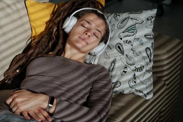 Jovem mulher serena com fones de ouvido deitada em um travesseiro em um quarto escuro e dormindo com música relaxante