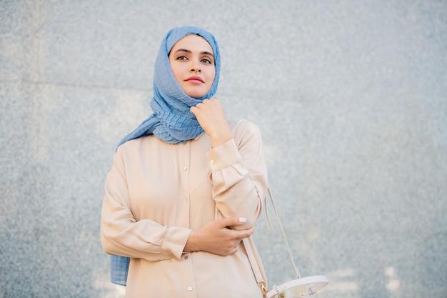 Jovem mulher serena em hijab e roupa casual em pé junto à parede de um edifício moderno em ambiente urbano