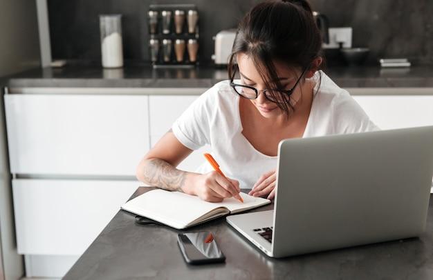Jovem mulher séria concentrada que usa notas da escrita do laptop.