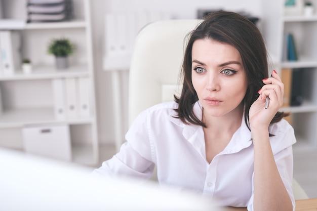 Jovem mulher séria de camisa branca segurando uma caneta enquanto olha atentamente para a tela do computador e rola os dados online