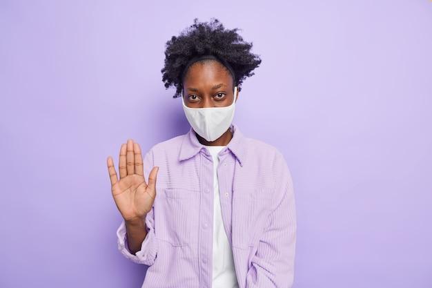 Jovem mulher séria de pele escura fazendo gesto de parar com a palma da mão para frente