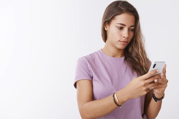 Jovem mulher séria e focada segurando um smartphone procurando tela editando selfie usando aplicativo de fotos, pensando o que escrever blog de mídia social, mensagens, procurando sinal de celular