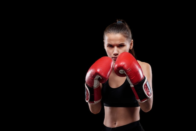 Jovem mulher séria e poderosa com roupas esportivas e luvas de boxe, olhando para você pronta para lutar contra um fundo preto
