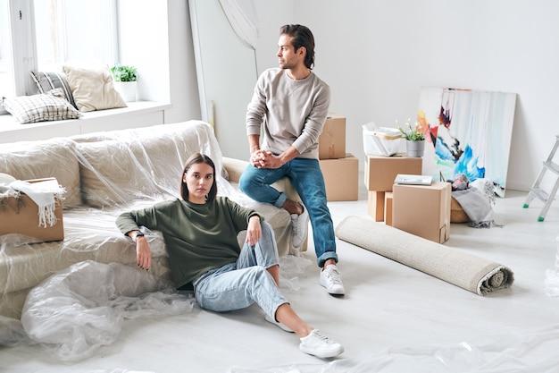 Jovem mulher séria em trajes casuais sentada no chão e olhando para você, enquanto o marido no sofá olhando pela janela da sala de estar