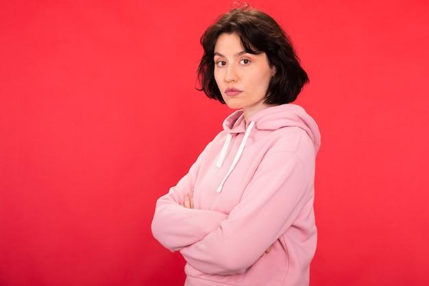 Jovem mulher séria em um moderno moletom rosa hippie posa com os braços cruzados sobre fundo vermelho