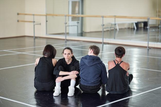 Jovem mulher séria fantasiada olhando enquanto está sentada entre três dançarinos no chão do estúdio de dança moderna