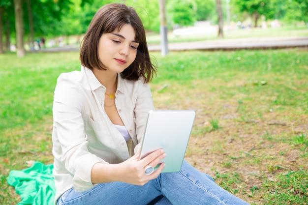 Jovem mulher séria que lê a notícia na tabuleta e que senta-se no gramado