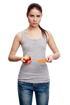 Jovem mulher séria segurando o comprimido em uma mão ee maçã em outro