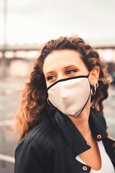 Jovem mulher sexy com máscara branca em um estacionamento
