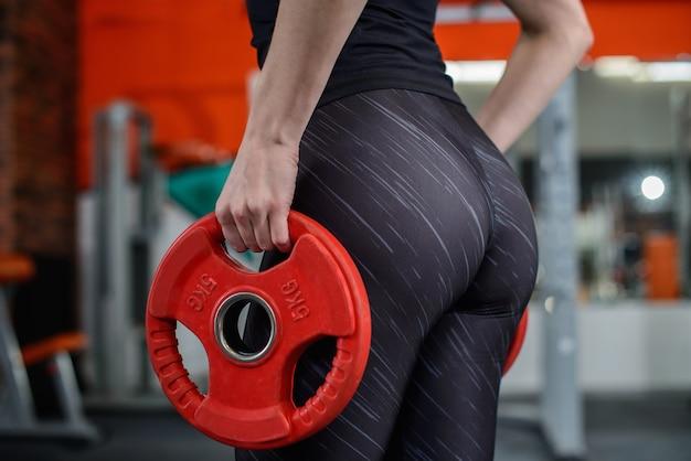 Jovem mulher sexy durante treino de fitness no ginásio